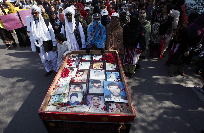 Des familles balouches transportent les portraits de leurs proches disparus tout au long de leur marche. Passage à Lahore, le 14 février 2014.