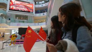 L'ouverture du XIXe congrès du parti communiste chinois est suivie avec attention sur écran dans un centre commercial de Pékin, le 18 octobre 2017.