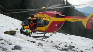 A helicopter takes away the human remains from Mont Blanc