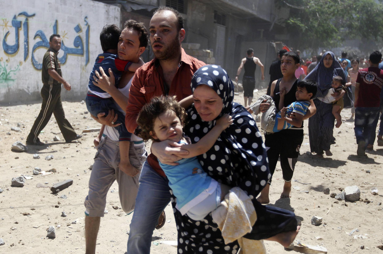 Palestinos fogem depois de ter suas casas atingida por bombas israelenses na Faixa de Gaza