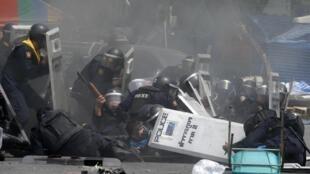 Policiais tentam ultrapassar as barricadas diante da sede do governo em Bancoc, na Tailândia, nesta terça-feira (18).