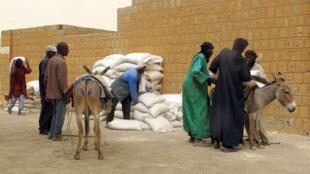 Distribution alimentaire devant la mosquée Djingareyber à Tombouctou, au Mali.