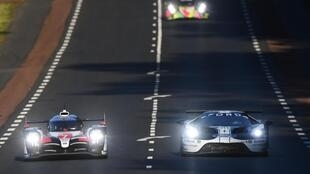 British driver Mike Conway (L) steers his Toyota, ahead German driver Andre Lotterer (C) in his Rebellion, during the second qualifying practice session at Le Mans, northwestern France, on 13 June 2019.