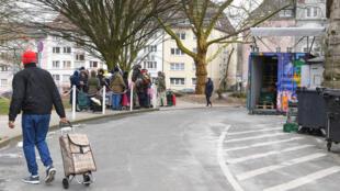 Beneficiários aguardam em frente à Ong Tafel, em Essen, oeste da Alemanha, que distribui alimentos à população desfavorecida.