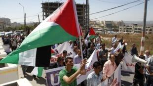 Палестинские активисты в Рамалле перед зданием ООН с палестинскими флагами требуют признания палестинского государства