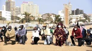Des manifestants posent un genou à terre, sur la corniche de Dakar, au Sénégal, le 9 juin 2020, en solidarité avec le mouvement Black Lives Matter.