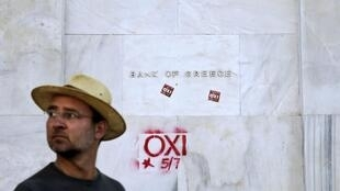 Devant la Banque nationale grecque, à Athènes, le 2 juillet. Sur le mur, un graffitit en faveur du «non».