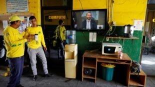 Les ambulanciers paramédicaux des Comandos de Salvamento regardent le président du Salvador, Nayib Bukele, à la télévision, alors qu'il annonce des mesures contre la maladie à coronavirus (Covid-19), à San Salvador, le 11 mars 2020.