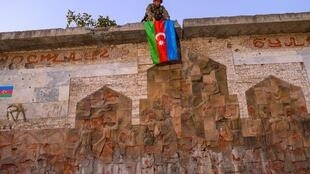 An Azeri soldier hangs the flag of Azerbaijan on a wall in Jabrayil
