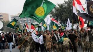 Bandeiras das milícias xiitas durante funerais do general iraniano Soleimani e sua equipa assassinos por forças americanas