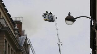 Firefighters fighting a fire on the roof of the luxury Ritz Paris hotel, 19 January 2016