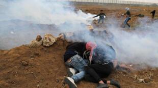 Manifestantes palestinos se protegem dos disparos do exército israelense, em Gaza.