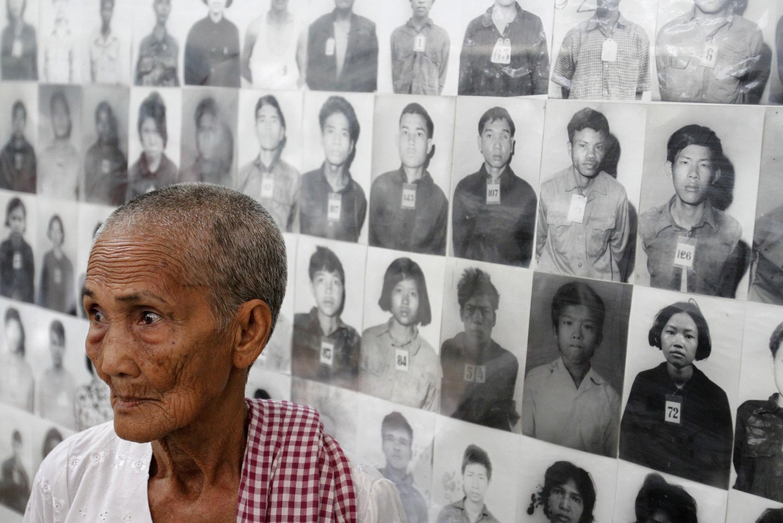 """Выжившая в геноциде """"красных кхмеров"""" 79-летняя Хем Саку перед портретами жертв режима Пол Пота в мемориале Пном Пеня 31 мая 2011."""