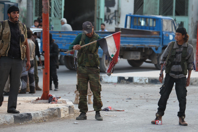 Một binh sĩ của Mặt trận Al-Nusra đốt cờ Syria, Ariha, 29/05/2015.