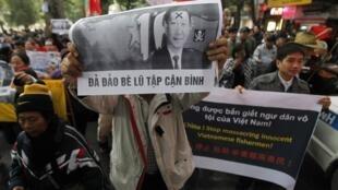 Một người biểu tình tại Hà Nội trương cao khẩu hiệu chống Trung Quốc ngày 9/12/ 2012.