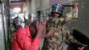 Askari polisi akimpia mmoja wa waandamanaji katika jengo moja wakati wa maandamano mjini Nairobi, Kenya, Mei 16, 2016.