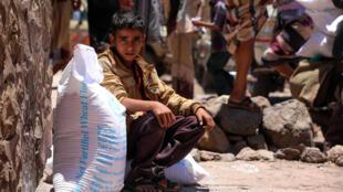Un garçon yéménite reçoit une aide du Programme alimentaire mondial (PAM) dans la troisième ville du pays, Taez, en octobre 2020.