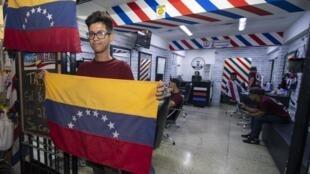 Un ancien étudiant en ingénieurie vénézulien tenant son drapeau devant le salon de coiffure dans lequel il travaille actuellement à Lima, en janvier 2019.