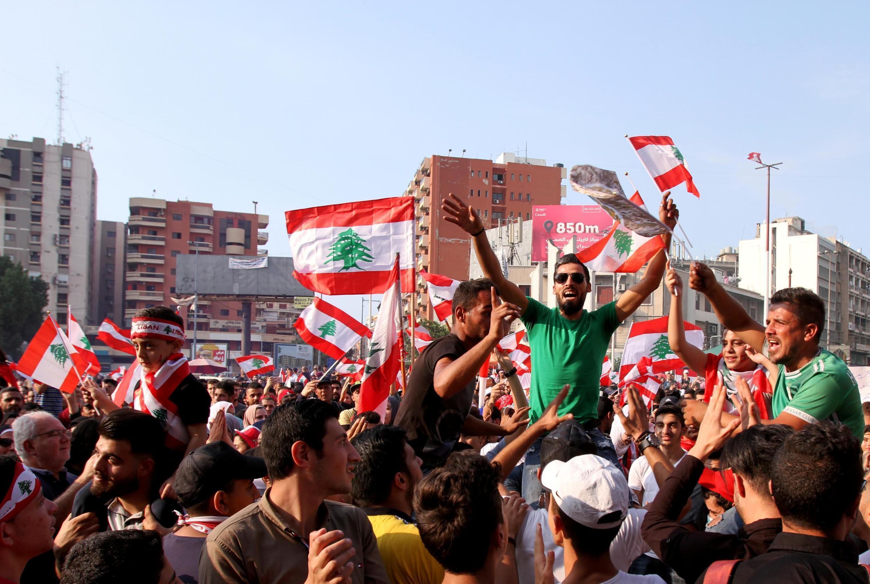 Des manifestants dans les rues de Tripoli la deuxième plus grande ville du Liban. (Madhi K en T-shirt vert, au centre, est porté en triomphe) le 22 octobre 2019.