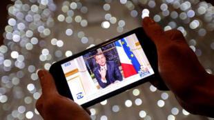 TT Pháp Emmanuel Macron được thấy trên màn ảnh điện thoại tại Marseille (Pháp), khi ông chúc Tết dân chúng ngày 31/12/2017.al New Year speech during a prime time news broadcast at the Elysee Palace in Paris, France, December 31, 2017.