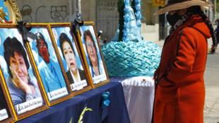 Una mujer mira fotografías de trabajadores de la salud fallecidos en la ciudad montañosa peruana de Puno en los Andes, cerca de la frontera con Bolivia, durante una protesta frente a una escuela de medicina local, el 26 de agosto de 2020.