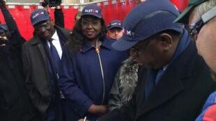 Le président sénégalais Macky Sall signe une dédicace aux côtés du directeur de l'usine Alsthom, Olivier Carnot.
