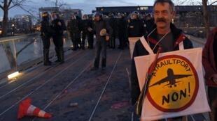 """Un manifestant brandit une pancarte pour dire """"non"""" au projet de construction d'un aéroport à Notre-Dame-des-Landes, le 15 décembre 2012."""