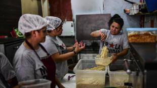 """Membros do movimento """"Movimiento Popular La Dignidad"""" servem uma sopa popular que beneficiam pelo menos 70 famílias pobres atingidas pela crise econômica na Argentina, em Buenos Aires, em 11 de janeiro de 2019."""