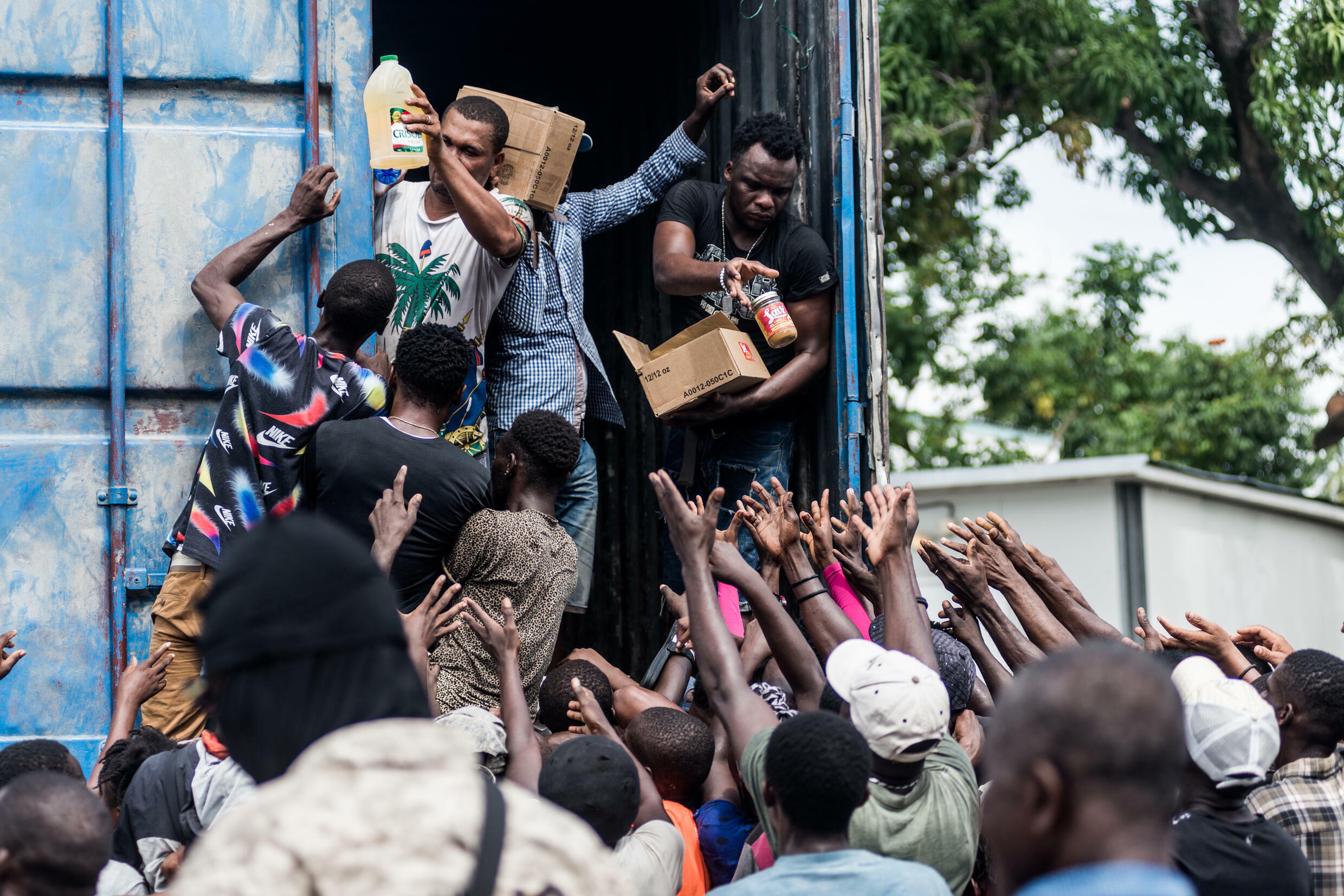 Men hand out supplies to a crowd of earthquake victims during the distribution of food and water in Les Cayes, Haiti, August 20, 2021