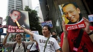 Protesters hold up placards with images of  Liu Xiaobo during a demonstration in Hong Kong