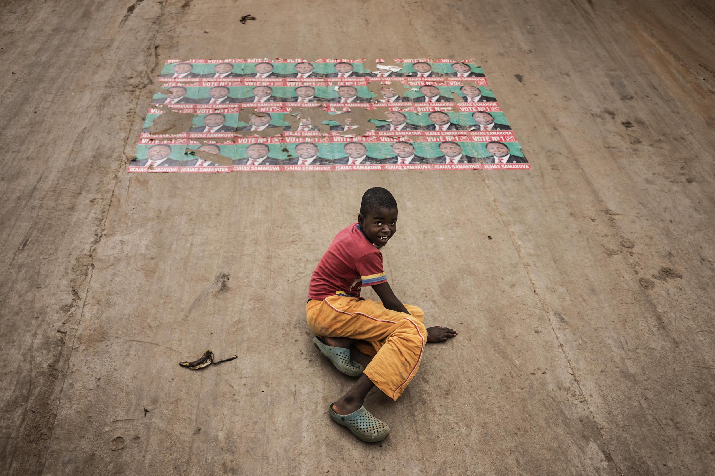 A Luanda, un enfant joue sous les affiches du candidat de l'Unita aux législatives de ce mercredi 23 août en Angola.