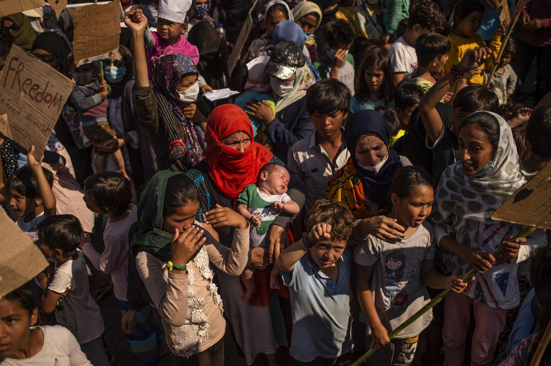 Una mujer carga con un bebé durante una protesta de refugiados y migrantes del quemado campamento de Moria cerca de Mitilene en la isla griega de Lesbos, el 12 de septiembre de 2020