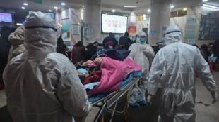 این عکس که در تاریخ ٢۵ ژانویه ٢٠٢٠ گرفته شده است، پرسنل پزشکی بیمارستان صلیب سرخ شهر ووهان را با یک بیمار مبتلا به  ویروس كرونا نشان میدهد .