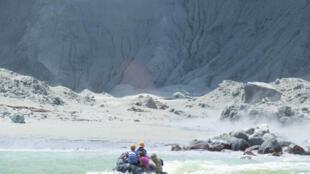 Туристические гиды эвакуируют туристов на лодке после извержения вулкана на острове Уайт-Айленд