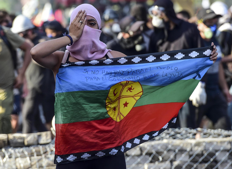 La bandera mapuche se vio a menudo en las manifestaciones que sacudieron Chile en el otoño de 2019. Aquí, una manifestante en Santiago, el 6 de diciembre de 2019.