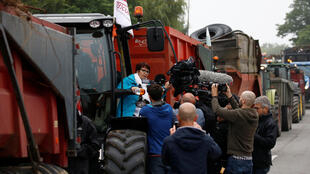 Christiane Lambert, President of France's farmer's union group FNSEA, talks to journalists as she stands on a tractor during a protest by French farmers to block the French oil giant Total refinery in Donges, France, June 11, 2018.