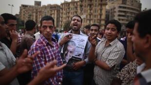 Discussion politique sur la place Tahrir au Caire le 26 mai 2012. Un électeur tient un portrait du candidat Hamdeen Sabbahi.