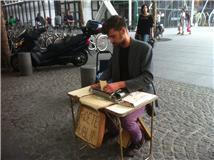 Antoine trabalha em uma mesinha improvisada, despertando a curiosidade dos passantes.