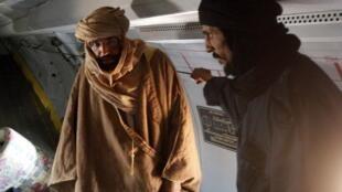 Seif al-Islam Kadhafi (G) dans l'avion qui l'emmène à Zenten après sa capture, le 19 novembre 2011.