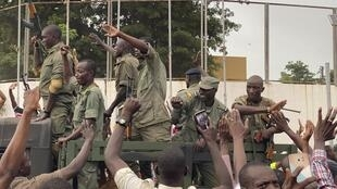 Malian soldiers cheer near Independence Plaza in Bamako, 18 August 2020.