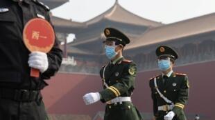 Unos paramilitares con mascarillas marchan en el exterior de la Ciudad Prohibida de Pekín el 1 de mayo de 2020
