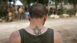 Un soldat israélien portant l'Etoile de David en tatouage, de retour en Israël, le 5 août, après avoir combattu dans la bande de Gaza.