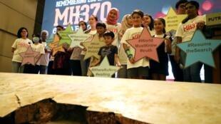 Les familles des victimes posent pour une photo de groupe avec des débris du vol MH370 de Malaysia Airlines lors de l'hommage aux victimes à Putrajaya en Malaisie, le 7 mars 2020.