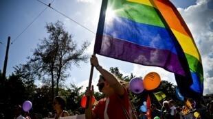 Une femme agite le drapeau arc-en-ciel de la communauté LGBT à Lisbonne, le 21 juin 2014.