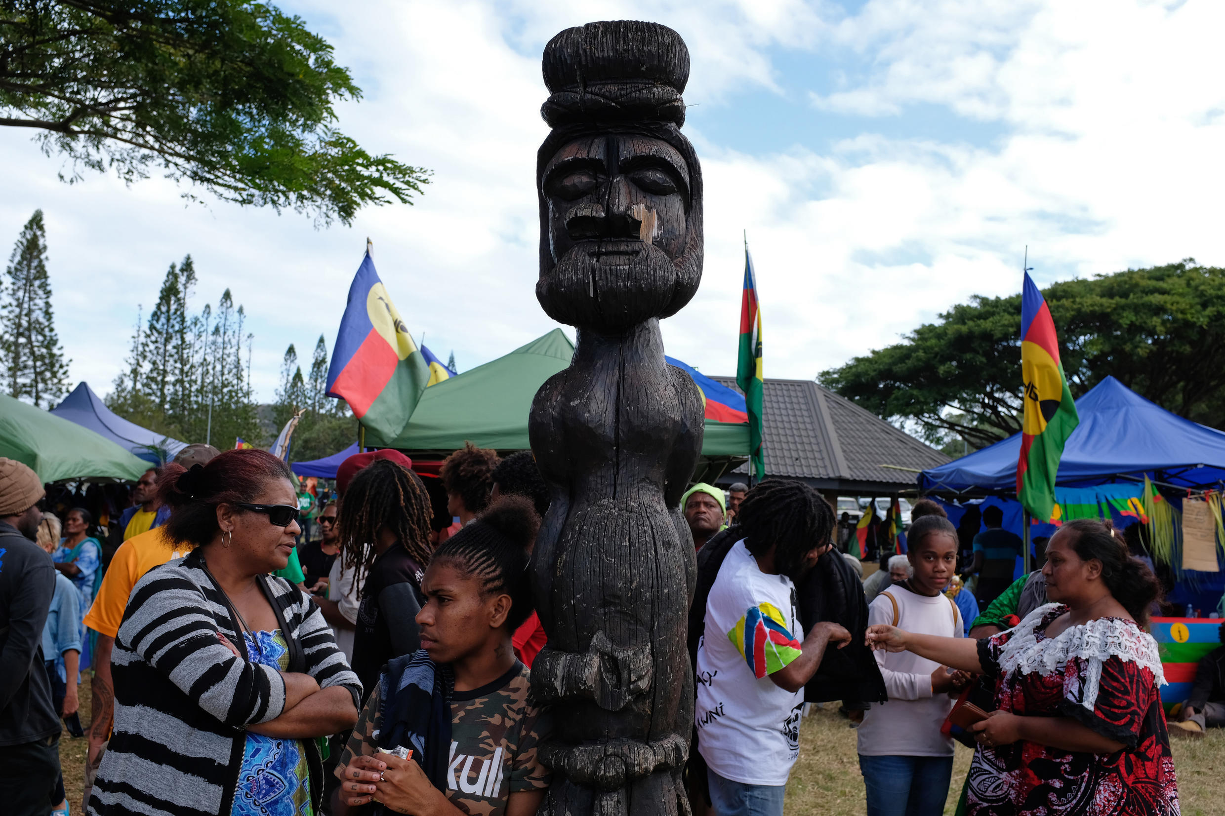 "People stand past a totem during the last meeting on 1 October, 2020 in Nouméa, of the Socialist Kanak National Liberation Front (FLNKS) campaign for ""YES"" to self-determination in New Caledonia's referendum."