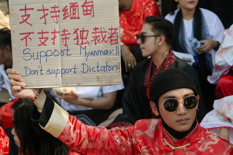 foto tirada em 11 de fevereiro de 2021, o modelo, ator e cantor Paing Takhon veste uma roupa tradicional chinesa enquanto segura uma placa durante uma manifestação contra o golpe militar em frente à embaixada chinesa em Yangon. Paing Takhon, que apoiou os protestos anti-golpistas do país, foi preso em 8 de abril, segundo informações, pois a junta caça mais de 100 celebridades por apoiarem o movimento.