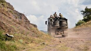 Des militaires arméniens transportent des pneus usagés à l'arrière d'un camion pour fortifier leurs positions à la frontière avec l'Azerbaïdjan, le 15 juillet 2020.