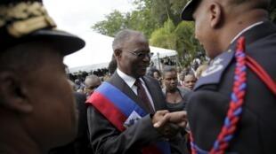 Le président provisoire, Jocelyne Privert salue un officier de la police national dans les jardins du palais présidentiel à Port-au-Prince, le 14 février 2016.