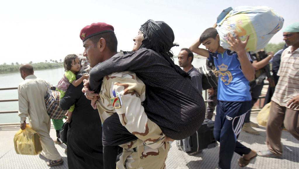 Иракский солдат помогает женщине эвакуироваться из зоны военных действий около города Рамади, 24 мая 2015.