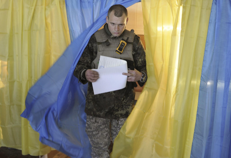 Soldado ucraniano deixa sessão eleitoral depois de votar neste domingo